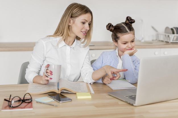 a-young-girl-attending-online-school-as-her-mother-watches-on