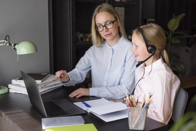 a girl attending online school as her mother provides guidance