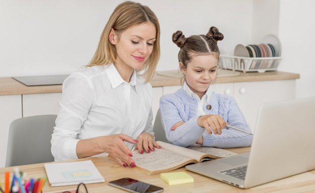 a parent helping her child navigate the first few days of online school