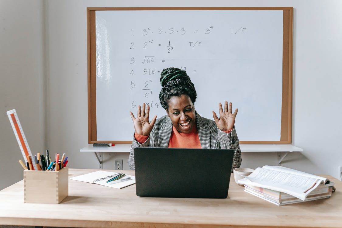 a teacher animatedly waving to her students during an online class