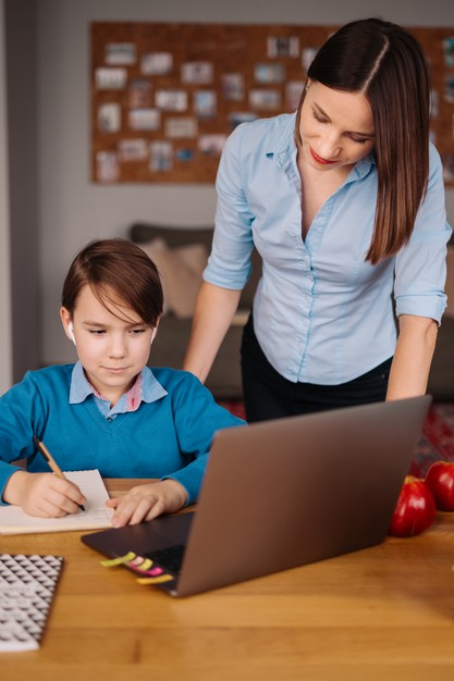 a young boy attending online school as his mother watches on
