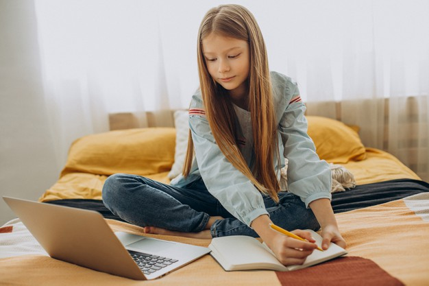a young girl taking notes during online clas