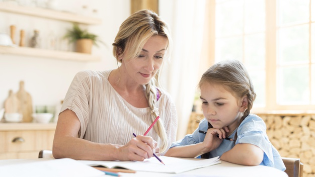 a young girl working on her SPAG homework with her mom