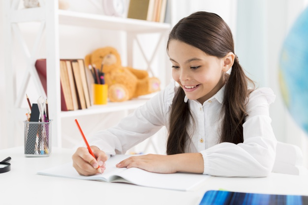 a young girl writing in a notebook
