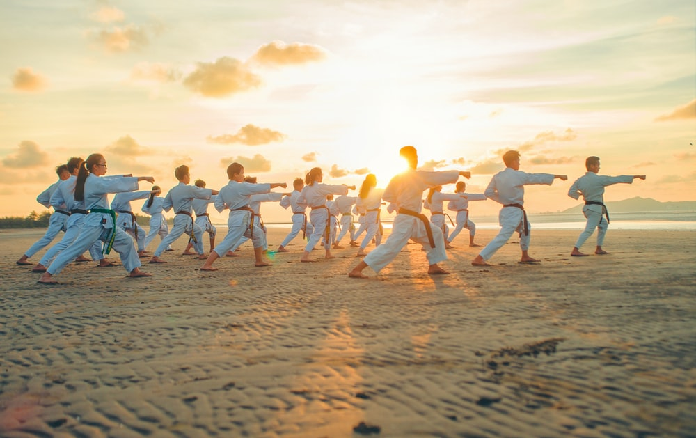 a class of teenagers practising martial art forms at the beach