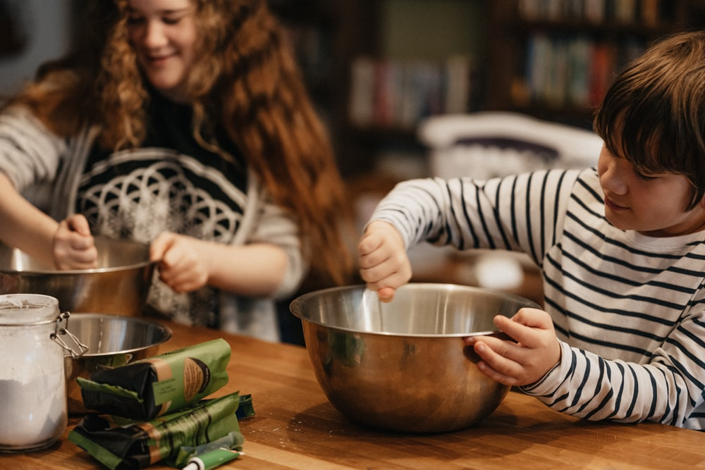 a teenage girl and young boy cooking in the kitchen